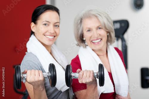 zwei frauen mit hanteln im fitnessstudio