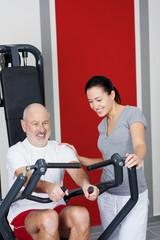 trainerin mit senior im fitnessstudio