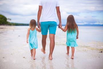 Rear view of father and his two kids walking by the sea