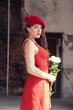Sensual sexy bride wearing red dress and hat standing in old hou
