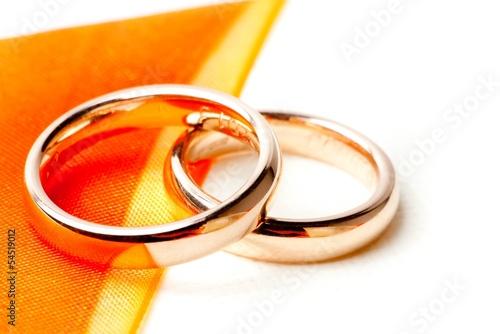 gold wedding rings near orange ribbon