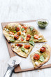 Gourmet flatbread sliced into portions on wooden board