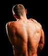 Muscular man with back neck ache isolated on black background