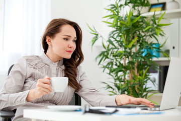 woman drinking coffee at desk