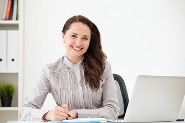 writting woman with laptop