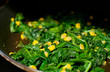 Cooking spinach, garlic and corn salad
