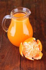 Full jug of tangerine juice, on wooden background
