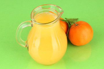 Full jug of orange juice, on wooden table on bright background