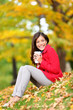 Happy woman drinking coffee in fall forest outdoor