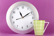 Cup tea and clock on purple background