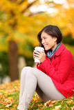 Autumn woman drinking coffee in fall forest