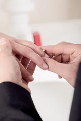 Man slipping an engagement ring onto her finger