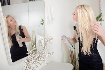 Woman applying hairspray to her hair