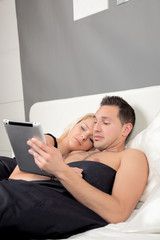 Couple lying in bed reading a tablet-pc