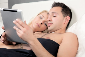 Couple reading a tablet-pc in bed