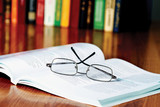 book with glasses on the desk against books