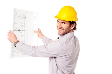 Smiling construction engineer reviewing blueprint