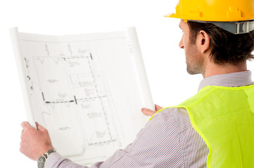 Man wearing hard hat reviewing the plan
