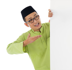 malay male with blank card during hari raya Eid al-Fitr celebrat