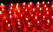 Firing candles in catholic church in red chandeliers
