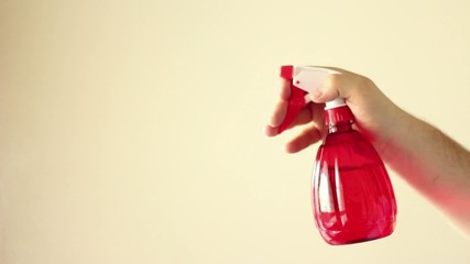 Hand using cleaning water sprayer with red liquid tank