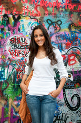 "Beautiful girl standing in front of ""John Lennon wall"" in Prague"