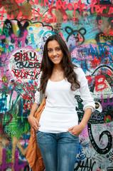 "Beautiful girl standing in front of ""John Lennon wall"" in Prague"