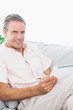 Happy man relaxing on his couch using tablet pc looking at camer