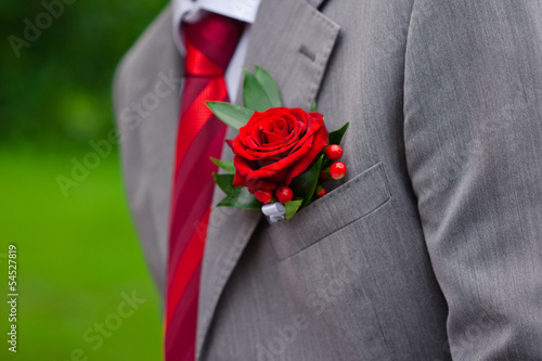 Red Rose boutonniere on grey suit