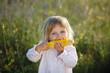 Child, corn - lovely girl eating corn on the cob in the garden