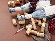 Old bottles of wine, grapes and corks on brown background