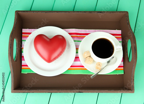 Wooden tray with breakfast, on color wooden background
