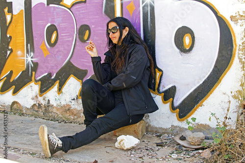 Young beautiful woman smoking in front of a graffiti wall