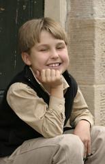 Smiling boy sitting on doorstep