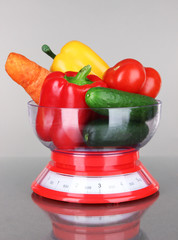 Fresh vegetables in scales on gray background