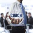 Elegant businessman holding the word coach