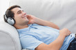 Cheerful man enjoying music lying on a couch
