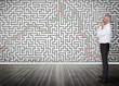 Thoughtful businessman looking at a maze on a wall