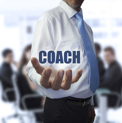 Elegant businessman holding the word coach