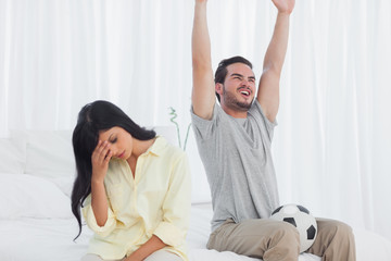 Woman annoyed at her partner watching football