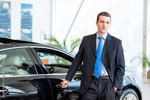 dealer stands near a new car in the showroom
