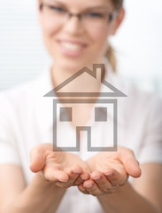 Real estate agent holding illustrated house in her hands