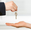 Real estate broker handing a key of a new flat to a woman