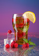 Iced tea with raspberries and mint on blue background