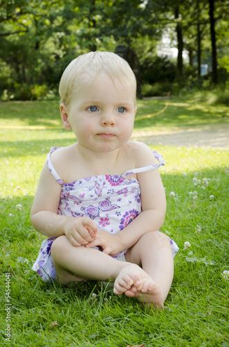 Kleines Kind sitzt auf Wiese und träumt