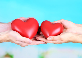 Hearts in hands on cloud background