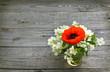 Poppy flower with sprigs of jasmine in a glass