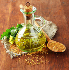 Jar of mustard oil and seeds with mustard flower