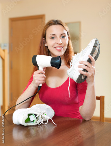 Happy red-haired housewife drying the running shoes with hair dr