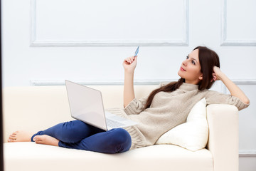 A woman with laptop is on the sofa